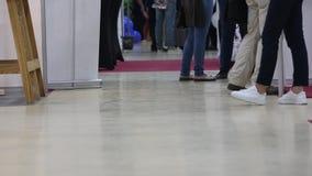 Οι επισκέπτες και οι εκθέτες του σε αργή κίνηση πυροβολισμού έκθεσης τέχνης από το κατώτατο σημείο δείχνουν τα πόδια των ανδρών κ απόθεμα βίντεο