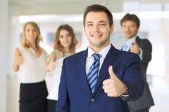 Οι επιτυχείς νέοι επιχειρηματίες που παρουσιάζουν αντίχειρες υπογράφουν επάνω Στοκ φωτογραφία με δικαίωμα ελεύθερης χρήσης