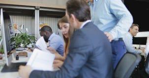 Οι επιχειρηματίες μελετούν τις εργασίες καθμένος στον υπολογιστή στο σύγχρονο γραφείο, ομάδα που αναλύει τα στοιχεία των εκθέσεων απόθεμα βίντεο