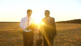 Οι επιχειρηματίες με την ταμπλέτα και το χαρτοφύλακα στα επιχειρησιακά κοστούμια τους συζητούν το σχέδιο για να εργαστούν μαζί στ φιλμ μικρού μήκους