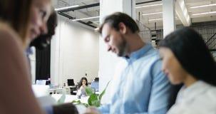 Οι επιχειρηματίες ομαδοποιούν τα έγγραφα εκθέσεων ανάγνωσης ενώ συνεδρίαση του 'brainstorming', businesspeople ομάδα που συζητά τ απόθεμα βίντεο