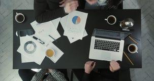Οι επιχειρηματίες παίζουν το βράχος-χαρτί-ψαλίδι Η ανωτέρω άποψη του πίνακα που καλύπτεται με τη γραφική παράσταση και το lap-top απόθεμα βίντεο