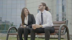 Οι επιχειρηματίες που κάθονται σε έναν πάγκο που εξετάζει ο ένας τον άλλον και τις χτυπώντας πυγμές αρχίζουν έπειτα τον αστείο χο φιλμ μικρού μήκους