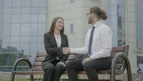 Οι επιχειρηματίες που συναντούν την εξωτερική συνεδρίαση εταιριών στον πάγκο που εισάγεται και που τινάζει δίνουν την επιχειρησια απόθεμα βίντεο