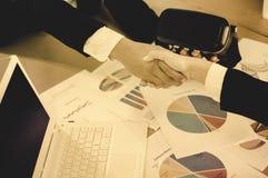 Οι επιχειρηματίες που τινάζουν τα χέρια συμφωνούν να αρχίσουν την επιχείρηση, έγγραφο στο μερίδιο πινάκων και ρυθμού ανάπτυξης κα στοκ εικόνα με δικαίωμα ελεύθερης χρήσης