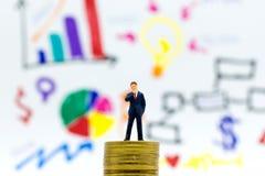 Οι επιχειρηματίες στέκονται στο σωρό των νομισμάτων, γραφικές παραστάσεις επίδειξης, περιθώρια κέρδους του υποβάθρου Χρήση εικόνα Στοκ Εικόνες