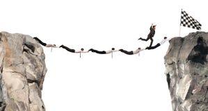 Οι επιχειρηματίες υποστηρίζουν τη γέφυρα για να φτάσουν στη σημαία Έννοια επιχειρησιακού στόχου επιτεύγματος Στοκ Εικόνες
