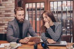 Οι επιχειρηματίες χρησιμοποιούν την ψηφιακή ταμπλέτα στον καφέ στοκ φωτογραφία με δικαίωμα ελεύθερης χρήσης