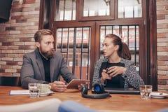 Οι επιχειρηματίες χρησιμοποιούν την ψηφιακή ταμπλέτα στον καφέ στοκ φωτογραφία