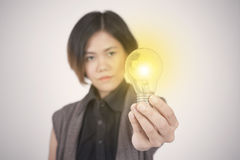 Οι επιχειρησιακές γυναίκες δίνουν τη λάμπα φωτός εκμετάλλευσης, έννοια των νέων ιδεών στοκ εικόνες