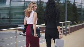 Οι επιχειρησιακές γυναίκες πηγαίνουν στα πλαίσια ενός εμπορικού κέντρου με τους φακέλλους για τα έγγραφα Δύο κορίτσια στα ακριβή  φιλμ μικρού μήκους