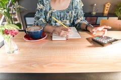 Οι επιχειρησιακές γυναίκες υπολογίζουν τη δαπάνη στον ξύλινο πίνακα με τον καυτό καφέ mocha και το κόκκινο λουλούδι Στοκ φωτογραφία με δικαίωμα ελεύθερης χρήσης