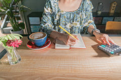 Οι επιχειρησιακές γυναίκες υπολογίζουν τη δαπάνη στον ξύλινο πίνακα με τον καυτό καφέ mocha και το κόκκινο λουλούδι Στοκ Εικόνες