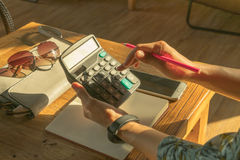 Οι επιχειρησιακές γυναίκες υπολογίζουν τη δαπάνη στον ξύλινο πίνακα στοκ φωτογραφία