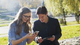 Οι επιχειρησιακοί άνδρες και οι γυναίκες χρησιμοποιούν μια ταμπλέτα και ένα τηλέφωνο στο πάρκο φιλμ μικρού μήκους