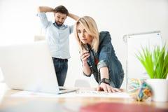 Οι επιδέξιοι νέοι εργαζόμενοι χρησιμοποιούν ένα σημειωματάριο Στοκ Εικόνες