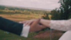 Οι εραστές αγγίζουν ήπια τα ο ένας του άλλου χέρια στο υπόβαθρο ενός όμορφου τοπίου Κινηματογράφηση σε πρώτο πλάνο των χεριών των απόθεμα βίντεο