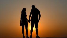 Οι εραστές ζεύγους σκιαγραφούν στο ηλιοβασίλεμα απόθεμα βίντεο