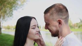 Οι εραστές στέκονται στην ακτή της λίμνης που μιλά αγκαλιάζουν και φιλούν απόθεμα βίντεο