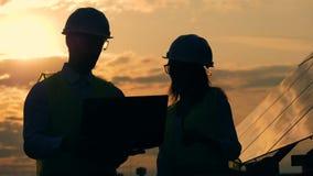 Οι εργάτες οικοδομών που εργάζονται σε ένα υπόβαθρο ηλιοβασιλέματος, κλείνουν επάνω απόθεμα βίντεο