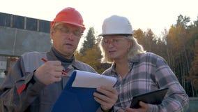 Οι εργάτες οικοδομών στο κράνος συζητούν την κατασκευή σύμφωνα με το πρόγραμμα σχεδίων απόθεμα βίντεο