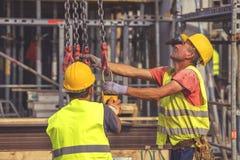 Οι εργάτες οικοδομών προετοιμάζονται στην ανύψωση της συγκεκριμένης φόρμας 5 στυλοβατών Στοκ Εικόνες