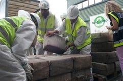 Οι εργαζόμενοι ανακτούν τα πακέτα φαρμάκων από ένα φορτηγό πριν από την καταστροφή του στοκ φωτογραφία