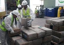 Οι εργαζόμενοι ανακτούν τα πακέτα φαρμάκων από ένα φορτηγό πριν από την καταστροφή του στοκ φωτογραφίες