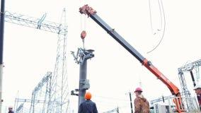 Οι εργαζόμενοι ανυψώνουν τον πύργο βάσεων που τοποθετεί στον ηλεκτρικό υποσταθμό διανομής φιλμ μικρού μήκους