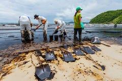 Οι εργαζόμενοι από το PTT χρησιμοποιούν το φτυάρι για να αφαιρέσουν το αργό πετρέλαιο Στοκ Εικόνα