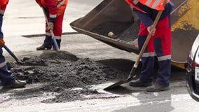 Οι εργαζόμενοι αφαιρούν την παλαιά άσφαλτο περικοπών φτυαριών από το δρόμο για την τοποθέτηση της νέας ασφάλτου φιλμ μικρού μήκους