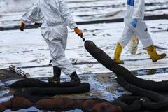 Οι εργαζόμενοι αφαιρούν το αργό πετρέλαιο από μια παραλία Στοκ Εικόνα