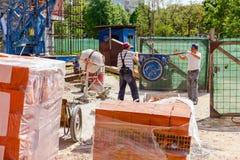 Οι εργαζόμενοι βοηθούν τον κινητό γερανό για να διαχειριστούν wheelbarrow στοκ φωτογραφία με δικαίωμα ελεύθερης χρήσης