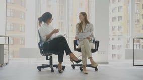 Οι εργαζόμενοι γραφείων, δύο γυναίκες που κάθονται στις καρέκλες που μιλούν, μια από τις γυναίκες λένε σε μια αστεία ιστορία τα ά απόθεμα βίντεο