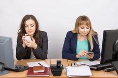 Οι εργαζόμενοι γραφείων είναι δεσμευμένες ιδιωτικά υποθέσεις στα κινητά τηλέφωνα στο γραφείο του Στοκ εικόνες με δικαίωμα ελεύθερης χρήσης