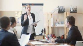 Οι εργαζόμενοι γραφείων κάθονται ήσυχα και ακούνε τις παρατηρήσεις από τον προϊστάμενο γυναικών φιλμ μικρού μήκους