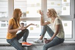 Οι εργαζόμενοι γραφείων που κουτσομπολεύουν κατά τη διάρκεια του καφέ σταματούν στοκ εικόνες