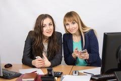 Οι εργαζόμενοι γραφείων συζητούν τα προσωπικά θέματα στα κινητά τηλέφωνα στο γραφείο του Στοκ φωτογραφία με δικαίωμα ελεύθερης χρήσης
