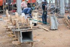 Οι εργαζόμενοι κάνουν το κιβώτιο στηλών και κρατούν από το γερανό για τη χτισμένη στήλη Στοκ εικόνα με δικαίωμα ελεύθερης χρήσης