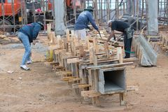 Οι εργαζόμενοι κάνουν το κιβώτιο στηλών και κρατούν από το γερανό για τη χτισμένη στήλη Στοκ Εικόνες