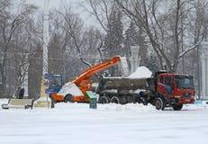 Οι εργαζόμενοι καθαρίζουν από το οδικό χιόνι σε VDNKh στη Μόσχα Στοκ Εικόνες
