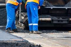 Οι εργαζόμενοι και οι ασφαλτώνοντας μηχανές στοκ φωτογραφία με δικαίωμα ελεύθερης χρήσης