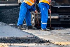 Οι εργαζόμενοι και οι ασφαλτώνοντας μηχανές στοκ φωτογραφίες