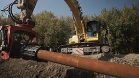 Οι εργαζόμενοι και ο εκσκαφέας σε ένα εργοτάξιο οικοδομής συσσωρεύουν την οδήγηση στο έδαφος, κατασκευή σωληνώσεων φιλμ μικρού μήκους