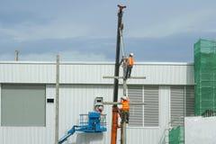 Οι εργαζόμενοι καλάθια εγκαθιστούν την οικοδόμηση ενός εργοστασίου και ενός κόκκινου γ στοκ φωτογραφία με δικαίωμα ελεύθερης χρήσης