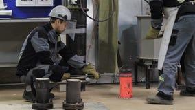 Οι εργαζόμενοι κρατούν τη μορφή και παίρνουν το υγρό μέταλλο με το μικρό φτυάρι απόθεμα βίντεο