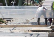 Οι εργαζόμενοι μεταγλωττίζουν την οδικά άμμο και το αμμοχάλικο στοκ εικόνα με δικαίωμα ελεύθερης χρήσης