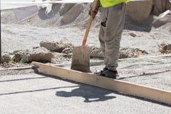 Οι εργαζόμενοι μεταγλωττίζουν την οδικά άμμο και το αμμοχάλικο στοκ φωτογραφίες