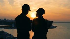 Οι εργαζόμενοι μιλούν, στεμένος σε ένα υπόβαθρο ηλιοβασιλέματος, πίσω άποψη φιλμ μικρού μήκους