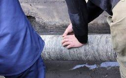 οι εργαζόμενοι μονώνουν το ruberoid υδροσωλήνων κατά τη διάρκεια της εργασίας επισκευής στοκ εικόνα με δικαίωμα ελεύθερης χρήσης